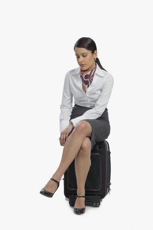 Air hostess sitting on her luggage and thinking