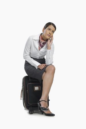 hotesse de l air: Hôtesse de l'air assis sur ses bagages et de la pensée LANG_EVOIMAGES