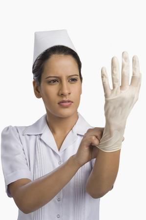 Female nurse wearing a surgical glove Stockfoto