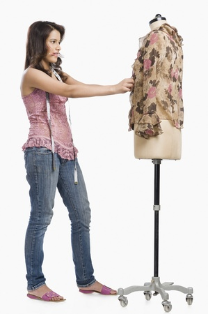 designer: Female fashion designer trying a dress on a mannequin
