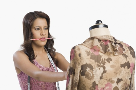 Female fashion designer trying a dress on a mannequin Stock Photo - 10125213