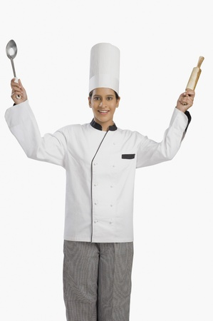 Female chef holding a rolling pin and a ladle Stock Photo