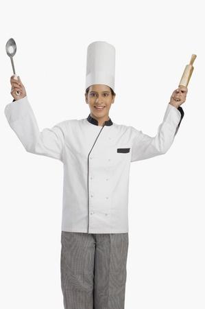 Vrouwelijke chef-kok met een deegroller en een pollepel