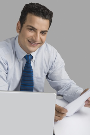Businessman holding a document and smiling Stock Photo - 10124605