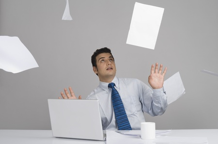 futility: Businessman sitting in office with papers falling around him