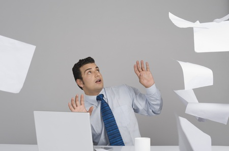 Businessman sitting in office with papers falling around him Stock Photo - 10124297