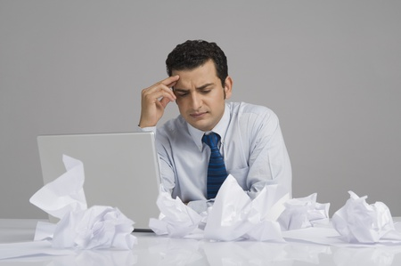 messy: Businessman looking worried with crumpled papers on desk