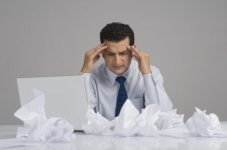 Businessman looking worried with crumpled papers on desk 免版税图像 - 10124390