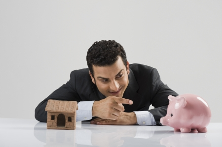 Businessman with a model home and a piggy bank Stock Photo - 10125321