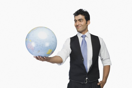 world at your fingertips: Businessman holding a globe and smiling