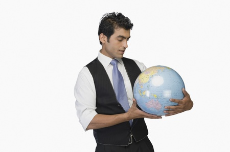 world at your fingertips: Businessman looking at a globe