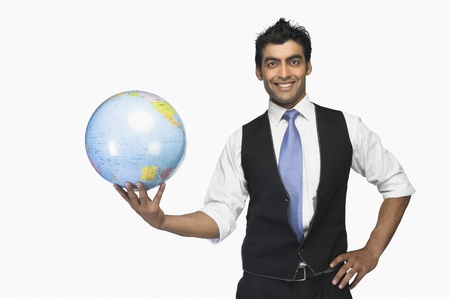 world at your fingertips: Portrait of a businessman holding a globe