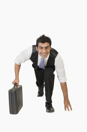 Businessman preparing for a race with a briefcase