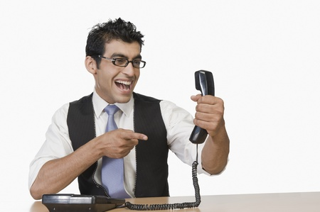 Businessman pointing at a telephone receiver and smiling Stock Photo - 10124315
