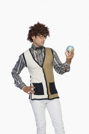 world at your fingertips: Man looking at a globe