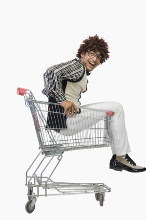 indian style sitting: Portrait of a man sitting in a shopping cart