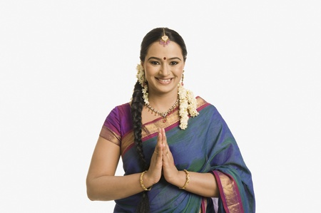 namaste: Mujer hace un gesto de saludo y sonriente LANG_EVOIMAGES