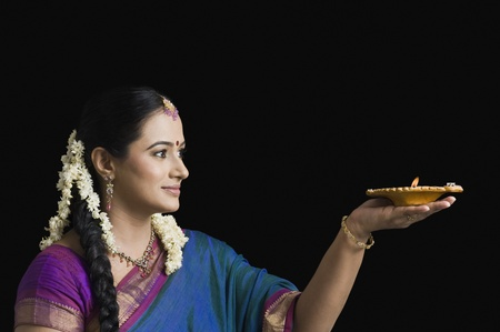 gajra: Woman praying with an oil lamp LANG_EVOIMAGES