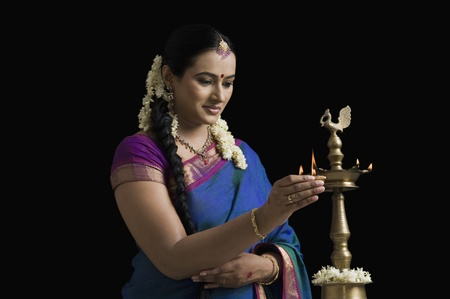 South Indian woman lighting an oil lamp