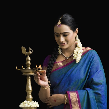 thinking woman: South Indian woman lighting an oil lamp