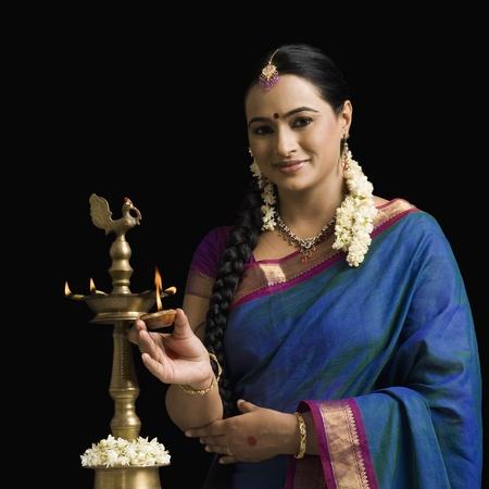 gajra: South Indian woman lighting an oil lamp