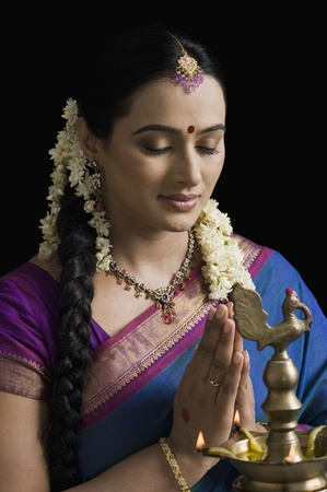 gajra: Woman praying in front of an oil lamp