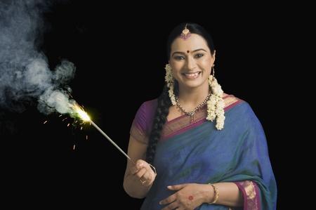 女性は線香花火のディワリ祭を祝う