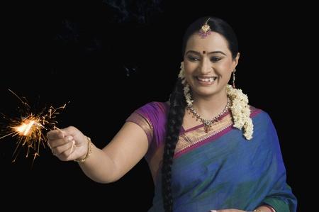 Woman celebrating Diwali festival with a sparkler 版權商用圖片