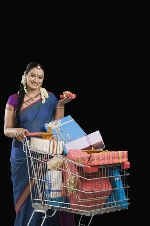 woman shopping cart: Woman carrying Diwali gifts in a shopping cart