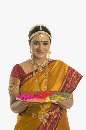 pongal: South Indian woman holding a tray of powder paints for rangoli
