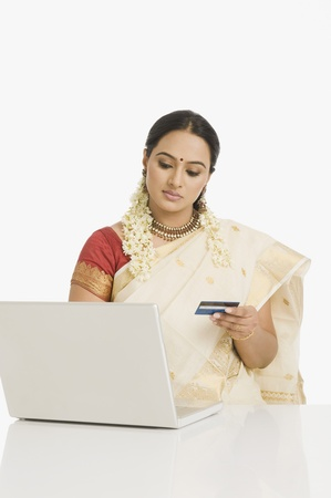 gajra: Woman holding a credit card and working on a laptop