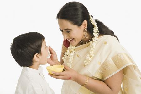 Woman feeding sweet to her son Фото со стока