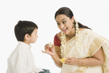 gajra: Woman feeding sweet to her son LANG_EVOIMAGES