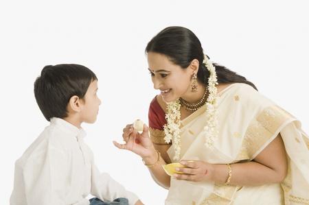 Woman feeding sweet to her son Stock Photo