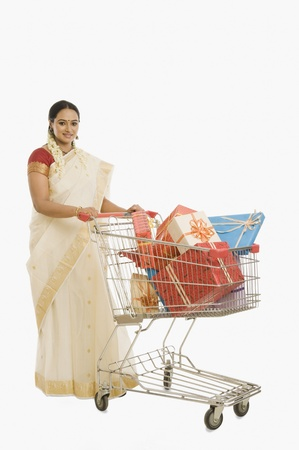 Woman carrying gifts in a shopping cart Reklamní fotografie - 10124324