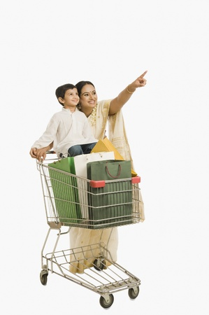 woman shopping cart: Woman pointing forward with her son standing on a shopping cart