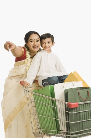 Woman pointing forward with her son standing on a shopping cart Stock Photo - 10124793