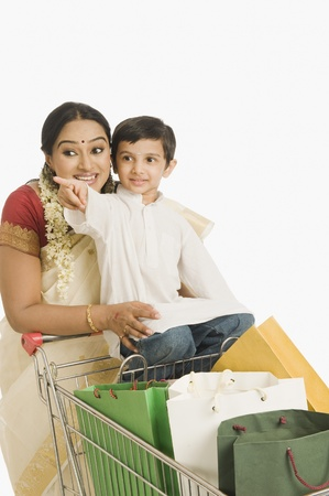 woman shopping cart: Woman with her son sitting on a shopping cart