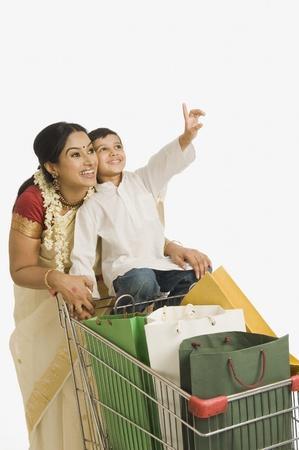 그녀의 아들은 쇼핑 카트에 앉아 여자 스톡 콘텐츠
