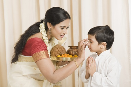 Woman applying tilak to her son
