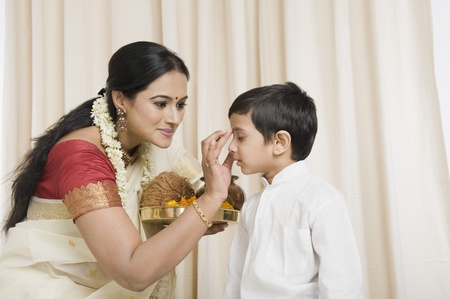 Woman applying tilak to her son Stock Photo - 10166240