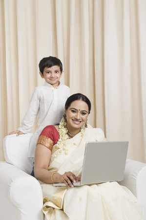 Woman using a laptop with her son standing behind her Stock Photo - 10124487