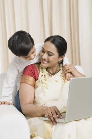 gajra: Woman using a laptop with her son standing behind her