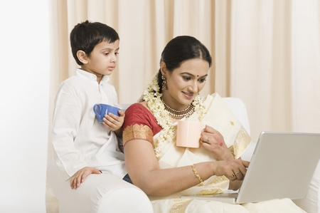 gajra: Woman using a laptop with her son and having coffee
