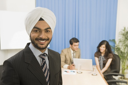 Businessman smiling with his colleagues in the background
