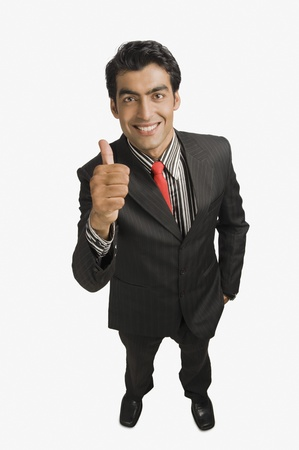 Portrait of a businessman showing thumbs up sign and smiling Stock Photo - 10125350
