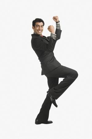 Zakenman glimlachend met zijn armen omhoog Stockfoto