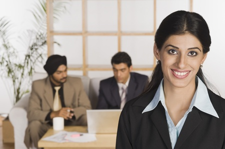 Businesswoman smiling with her colleagues in the background Stock Photo