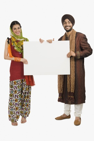 Portrait of a Sikh couple holding a blank placard Stock Photo - 10124694