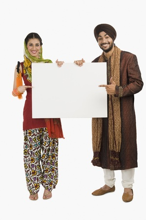 Portrait of a Sikh couple holding a blank placard Stock Photo - 10125092
